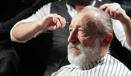 Bearded old man, retired, sitting in a Barber shop, barbershop for a haircut. A Barber cuts the hair of a gray-haired elderly man, an aged man, a pensioner.