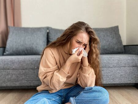 Young girl blows her nose using a paper napkin. The girl is sitting at home on outpatient treatment. Self-isolation prevention of coronavirus.