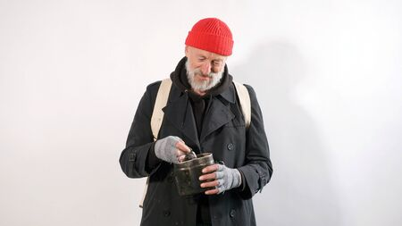 homeless Man, an old man with a gray beard in a hat smiling holding in his hand financial aid, dollars, isolated white background.