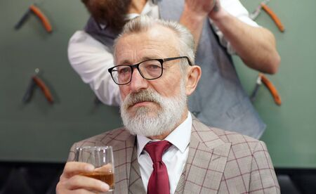 Rich old man, retired, gray-haired man with a beard evaluates his haircut and drinks whiskey, cognac.