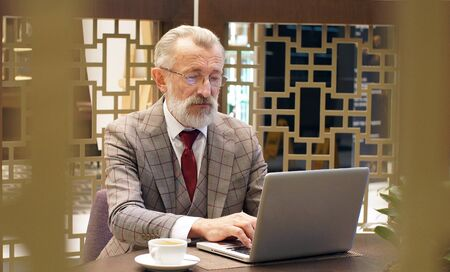 Stylish, fashionable focused elderly man, retired, writer in glasses and a classic suit working on a laptop in an office, restaurant, cafe, close-up.