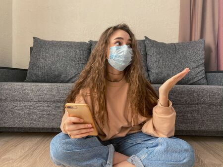 home quarantine Concept, a young woman wears a protective mask at home. prevention of COVID-19.