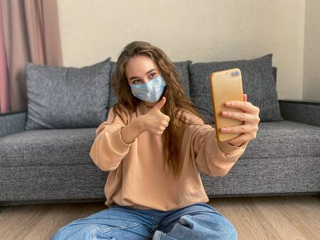 Caucasian young woman wearing a medical mask sitting at home on self-isolation during the coronavirus pandemic. A woman talks via video link with friends and relatives using a smartphone.