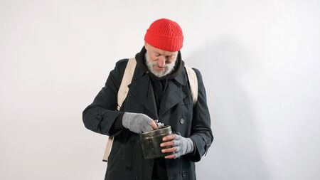 Old man with a beard, a homeless man, an elderly man dressed in a coat and a red hat looks at the dollars that were given to him and smiles. The concept of homeless effort. Stok Fotoğraf