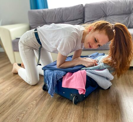 red-Haired girl wants to go on vacation, travel. A woman with a travel suitcase and a smartphone is going to go on vacation. The concept of vacation, travel. Zdjęcie Seryjne