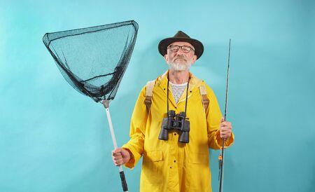 Happy fisherman with a fishing rod and binoculars posing on an isolated background, Studio shot. 版權商用圖片