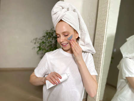 Beautiful woman after a shower in a towel on her head wants to apply a cosmetic mask on her face at home.