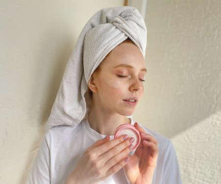 Cute woman takes care of her facial skin wants beautiful healthy skin.