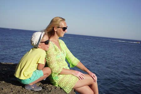 mother and son enjoy the seascape on a Sunny day, sitting by the sea on a high cliff, a large rock.