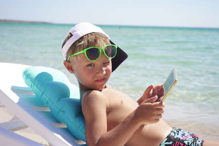 Blonde child sitting on the beach on a Sunny summer day playing on a tablet. Dependence on gadgets.