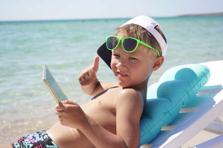 Tanned child shows a thumbs up resting on the beach and playing on a tablet while lying in a sun lounger. Cute boy uses tablet on the beach on a Sunny summer day.