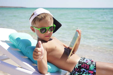 portrait of a child relaxing on the beach against the sea. he uses a tablet computer while lying on a chaise longue. concept of vacation at the sea. Stock Photo