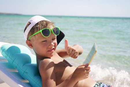 cute boy sitting on a sun lounger by the sea on the beach and playing on a tablet computer on a Sunny clear day. Concept of vacation at the sea. Stock Photo