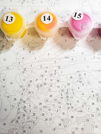 painting by numbers for beginners, drawing on canvas close-up, top view.
