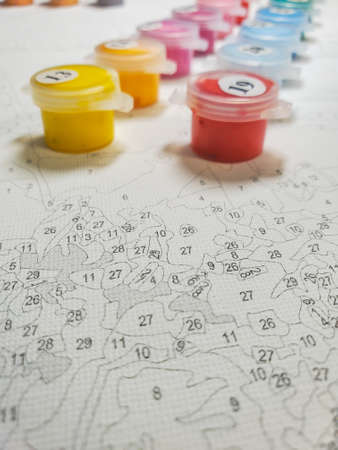 Painting on canvas by numbers and numbered jars of paint on the background of the canvas. Paint out of focus