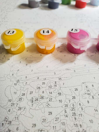 drawing on canvas by numbers and numbered forms with bright colors on the background of the canvas.