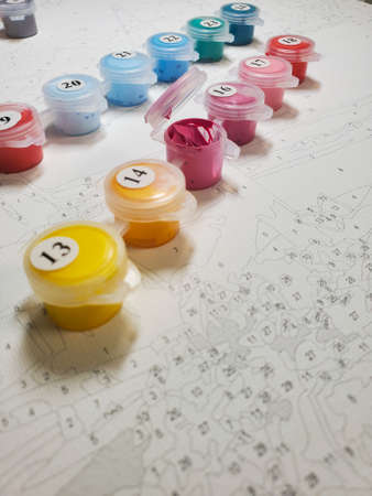 lots of bright acrylic paints on canvas. drawing by numbers. lots of bright acrylic paints on canvas. drawing by numbers. Selective focus. Standard-Bild