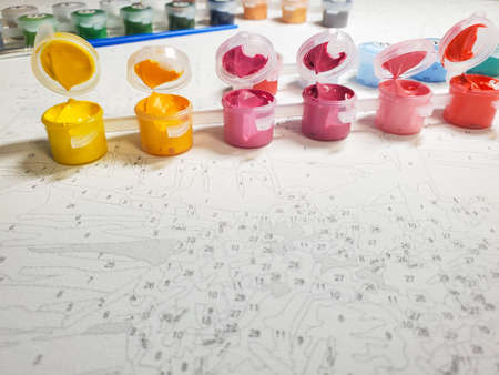 drawing on canvas by numbers and numbered forms with bright colors on the background of the canvas. Selective focus.