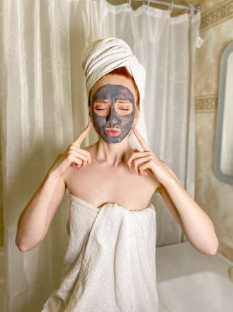 An attractive woman with a moisturizing clay mask on her face