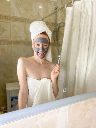 A young woman applies a nourishing gray clay mask