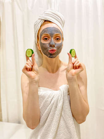 young woman with a towel on her head, a gray clay mask on her face, and a slice of cucumber in her hand. Standard-Bild