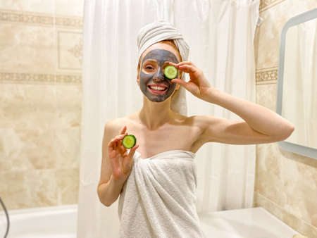 A young woman with a towel on her head, a gray clay mask on her face, and a slice of cucumber in her hand. Standard-Bild