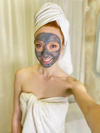 woman after a shower with a towel on her head applied a moisturizing gray clay mask to her face in the bathroom. woman with a clay mask on her face, a selfie.