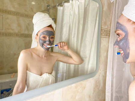 beautiful woman with a clay mask on her face and brushing her teeth