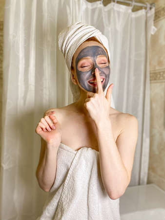 A young woman with a towel on her head, a gray clay mask on her face Standard-Bild