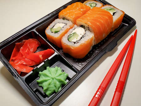 Contactless food delivery under quarantine from coronavirus. Delivery of food and sushi rolls.