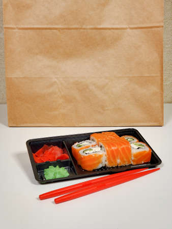 Delicious sushi rolls are served in plastic packaging on an isolated white table background.