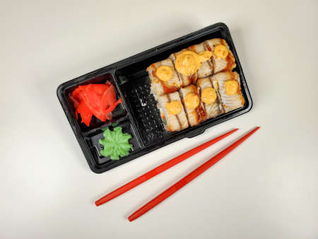 japanese sushi rolls for dinner or lunch on an isolated white background. The concept of delivery of Japanese cuisine.
