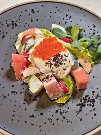 Close-up of a salad with poached egg and red caviar on a black plate, a beautiful salad serving.