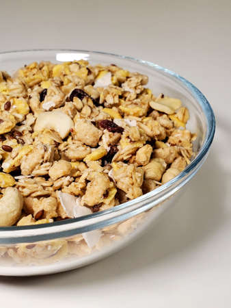 Muesli with nuts and dried fruits in a bowl on a white table Standard-Bild