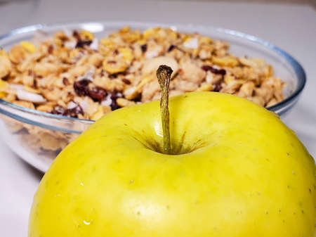 Lots of whole grain cereal for breakfast, green apple in the foreground