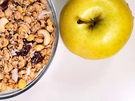 Green apple and breakfast cereal and muesli in a bowl on a white background. close-up Standard-Bild