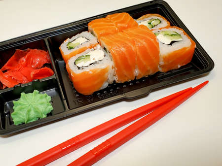 food Supplies. Sushi and rolls with salmon and shrimp. The concept of food delivery on self-isolation