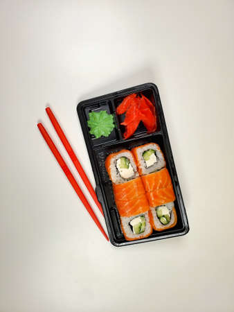 Delicious sushi rolls are served in plastic packaging on an isolated white table background