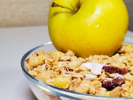 Muesli in a transparent plate close-up and a green apple on top