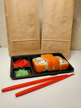 Contactless food delivery under quarantine from coronavirus. Delivery of food and sushi rolls Standard-Bild