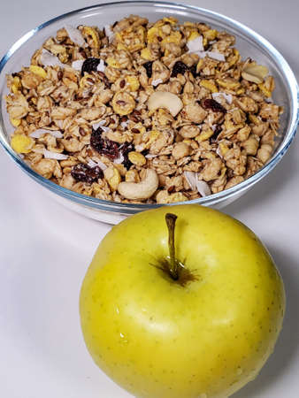 Close-up of muesli and various breakfast cereals and a healthy green apple