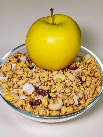 Healthy Breakfast green apple and muesli with nuts and dried fruits in a bowl on a white table