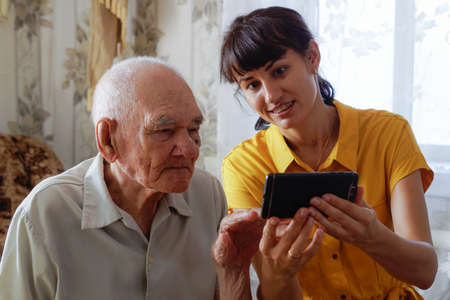 a man of the 90s with an adult granddaughter, sitting together on a cozy sofa with a phone in his hands, looking at photos. a woman in a yellow dress teaches the older generation how to communicate on a smartphone and the Internet while enjoying the weekend.
