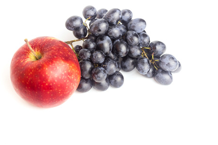 Red apple and a bunch of blue grapes, isolated on a white background