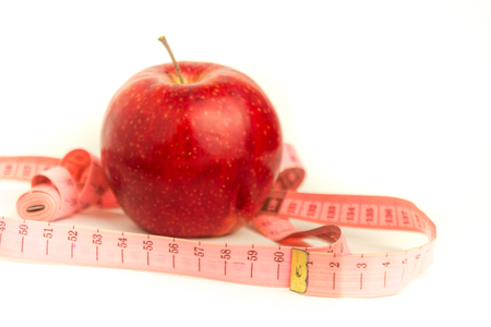 Bright red apple and pink measuring tape on a white background