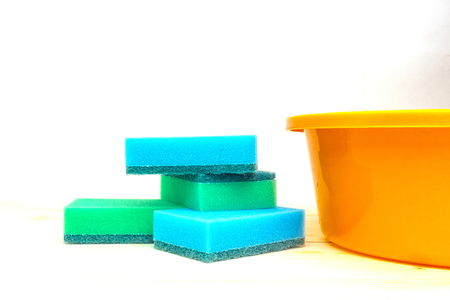 Colorful sponges and an orange basin for cleaning the premises on a light background.