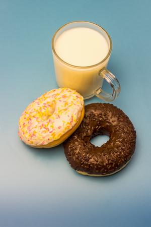 Donuts in glaze and milk in a glass cup on a blue background
