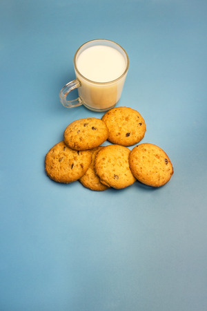 Cookies with chocolate shavings and milk in a glass cup, red plaid on a blue background