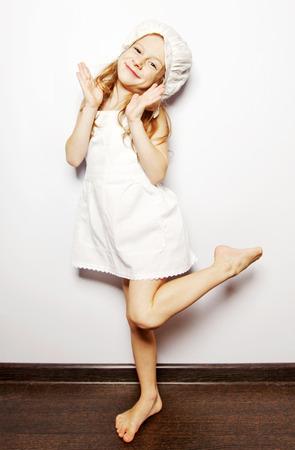 petite fille avec robe: petite fille souriante en robe blanche danse Banque d'images