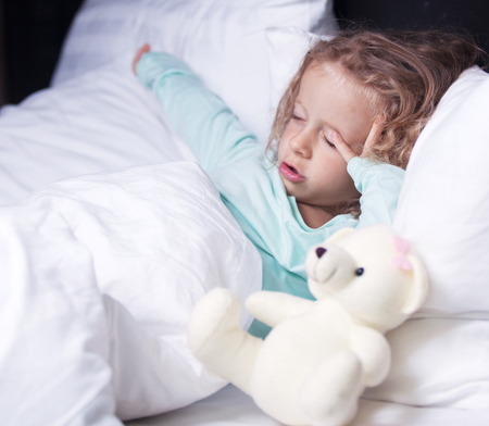 little girl stretches in bed with a toy bear photo